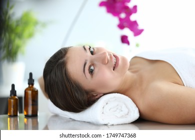 Happy girl is lying in massage room and smiling. Improve health and well-being. Muscle tension after heavy physical exertion or hard day. Maintain vitality body and strengthen immune system