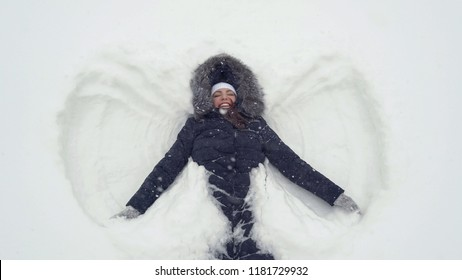 Happy girl lying on a snow and shows angel.
