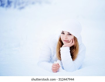 Happy girl lying  on the snow in winter