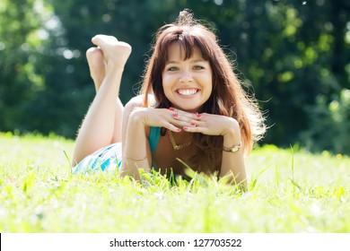 Happy girl lying outdoor in grass meadow