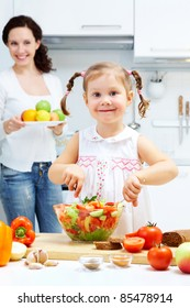 Happy girl mixing salad in bowl while woman holding plate full of fruits in the background