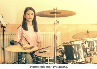 Happy girl in music therapy by playing drum kit on music room. Beautiful young girl drummer with drumsticks playing drums and cymbals. Female drummer. toned