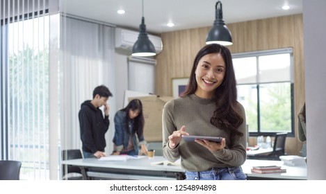Happy girl in the office.female looking on tablet screen coworkers discussing in background