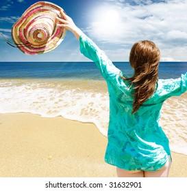 Happy girl on the beach against blue sea