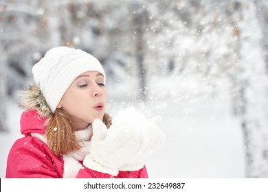 happy girl on a frosty winter walk on the street blows snow from hands