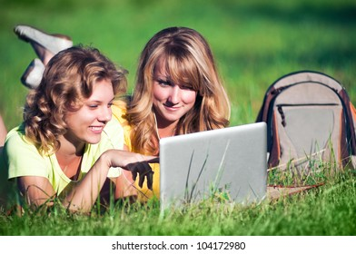 Happy girl on green grass with laptop