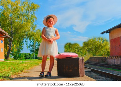 Happy girl on a railway station, waiting for the train with vintage suitcase. Traveling, holiday and chilhood concept. Travel insurance concept. Travel, tourism, summer vacation and family concept.