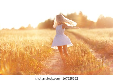 happy girl on the road in a wheat field at sunset