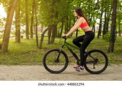 Happy girl over a bicycle in the park, lifestyle sport concept