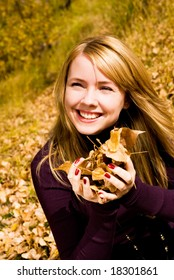 happy girl in the park with yellow leaves in her hands