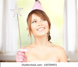 happy girl in party cap with magic wand