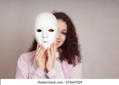 happy girl peeking behind mask