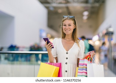 Happy girl with phone and colorful shopping bags in a shopping center. Quick and easy to order online