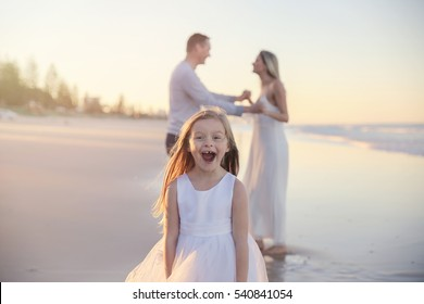 happy girl photo bombing her parents on the beach, toning