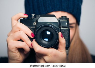 happy girl photographed in vintage camera, winter concept, studio photo isolated on a gray background