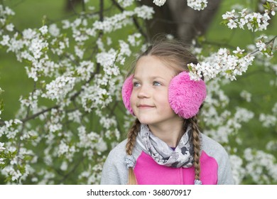happy girl in pink earmuffs looking up near blooming tree by springtime