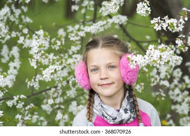 happy girl in pink earmuffs portrait near blooming tree by springtime