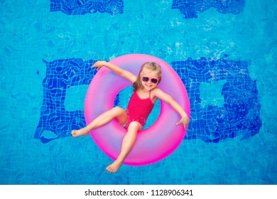 happy girl in pink rubber ring bathes in a pool