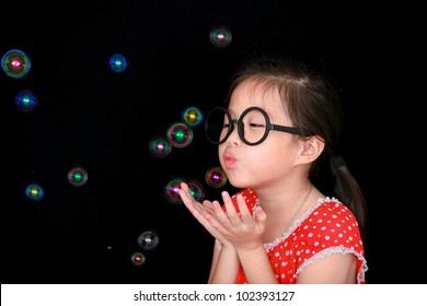 Happy girl play with soap bubbles isolated black background
