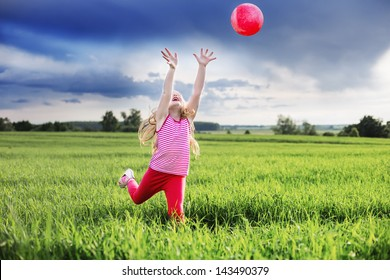 happy girl playing a ball on the meadow filled
