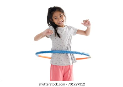 Happy girl playing hula hoop on white background