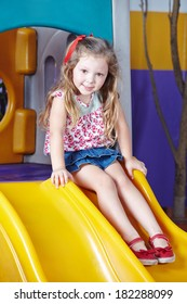 Happy girl playing on a slide in a kindergarten