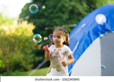 Happy Girl Playing with Soap Bubbles