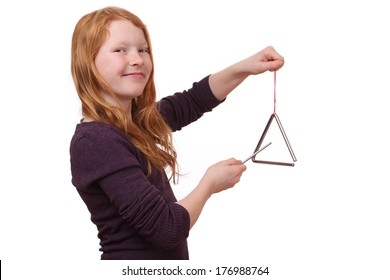 Happy girl playing a triangle instrument on white background
