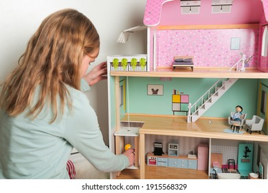 Happy girl plays with doll house and dolls. Happy child.