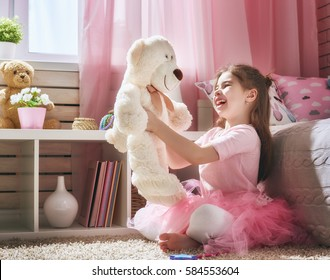 Happy girl plays with teddy bear at home. Funny lovely child is having fun in kids room.