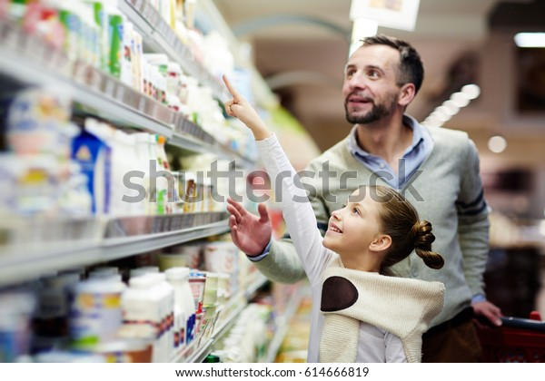 Happy Mädchen, das auf eine Packung Joughururt im oberen Regal im Supermarkt