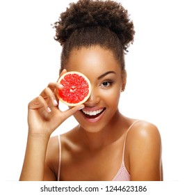 Happy girl with pomelo. Photo of african american girl holding a half of pomelo in front of her face and smiling on white background. Skin care and beauty concept.