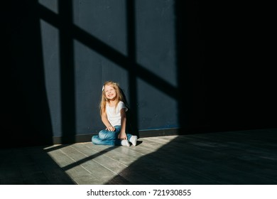 Happy girl portrait siting on gray background wooden floor room window sunny day