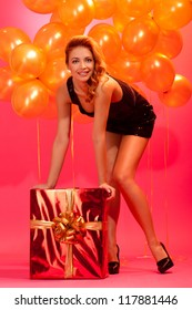 happy girl posing with gift box against balloons and pink background