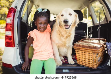 Happy girl posing with her dog in car