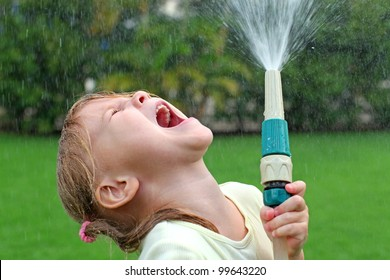 Happy girl pours water from a hose