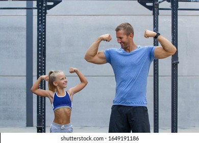 happy girl power strong girl showing muscles to fitness dad