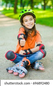 Happy girl in a protective helmet and protective pads for roller skating sitting on the road and showing thumbs up
