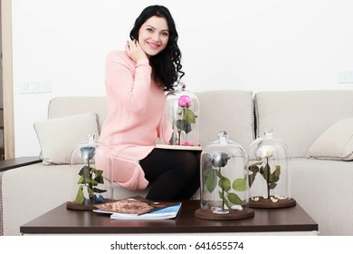 happy girl with puprle pose in glass flask, received as a gift, in modern apartment