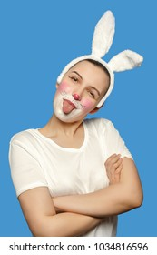 happy girl with rabbit makeup and ears on blue background show her tongue smiling