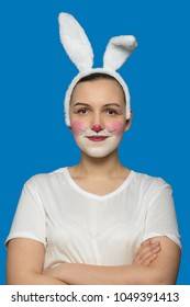 happy girl with rabbit makeup and ears on blue background looking smiling