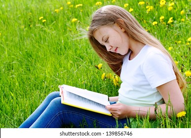 Happy girl reading book and sitting on green grass