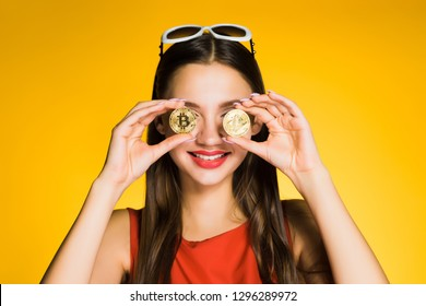 happy girl in red dress holds golden bitcoins in hands and smiles