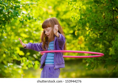 happy girl with red hair with a hula-hoops