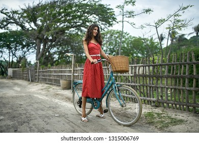 Happy girl in red polka dot dress and white sandals stands with a blue bike on the dirt road on the background of the wooden fence and tropical trees and the sky. She looks forward with a smile.