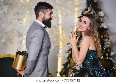 Happy girl rejoice at the gift with bow in festive room near christmas tree. Handsome romantic man hiding a gift box behind his back surprising his girlfriend on New Year. atmospheric festive moments.