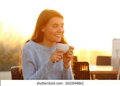 Happy girl relaxing drinking coffee at sunset sitting in a cafe terrace