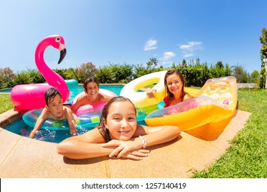 Happy girl relaxing with friends in outdoor pool