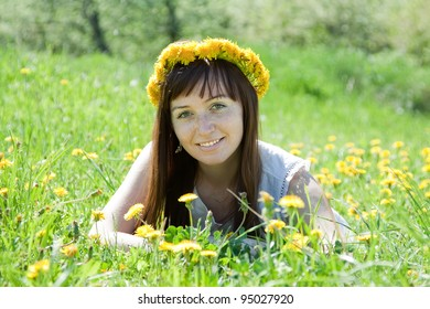 Happy girl relaxing outdoor in dandelion meadow
