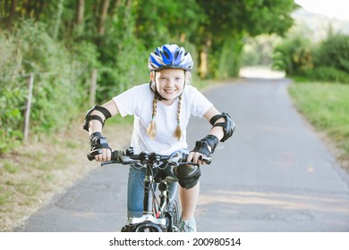 Happy girl riding bike with helmet and protection in the park, summertime